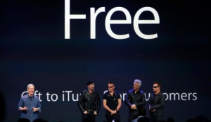 Apple CEO Tim Cook stands with Irish rock band U2 as he speaks during an Apple event announcing the iPhone 6 and the Apple Watch at the Flint Center in Cupertino